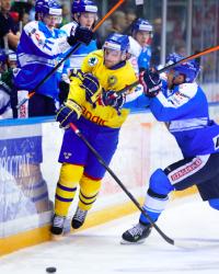 Sveriges Tom Wandell blir tacklad av Finlands Topi Jaakola under ishockeymatchen i Channel One Cup mellan Finland och Sverige den 22 december 2013 i Sochi. Foto: Joel Marklund / BILDBYRÅN